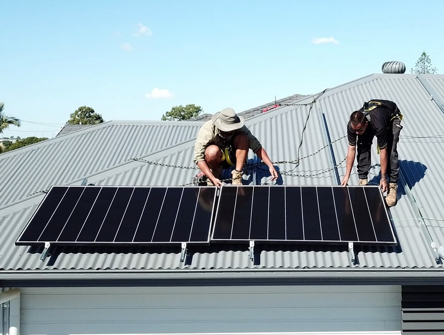two men installing solar panels on a residential rooftop property