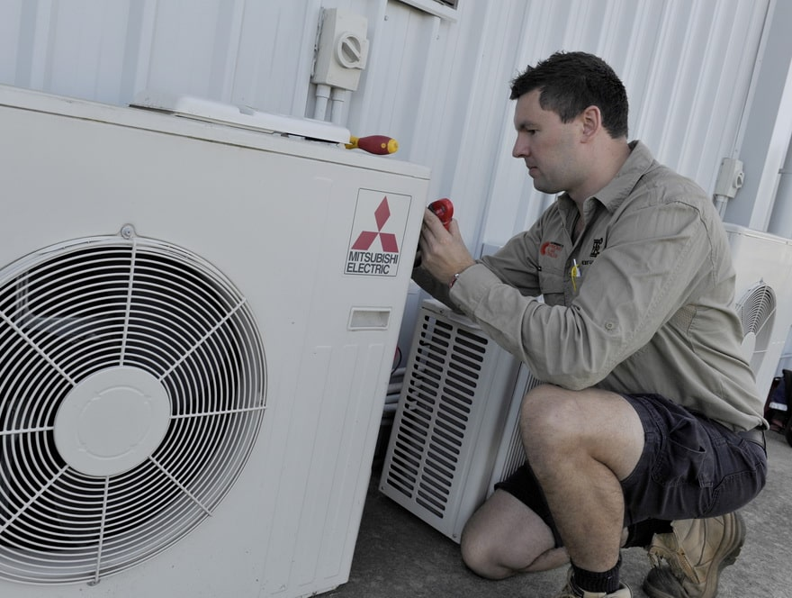 expert electrical employee setting up an air conditioning system at a commercial property