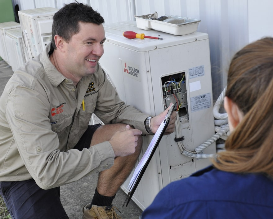 Expert electrical employee advising commercial client on air conditioners