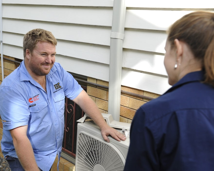 Expert electrical employee advising residential client on air conditioners