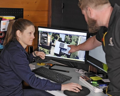 expert electrical employees discussing solar panels on a monitor screen