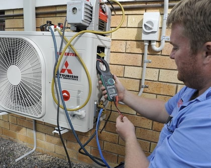 expert electrical employee testing the working status of an air conditioning unit