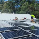 people installing solar panels on roof